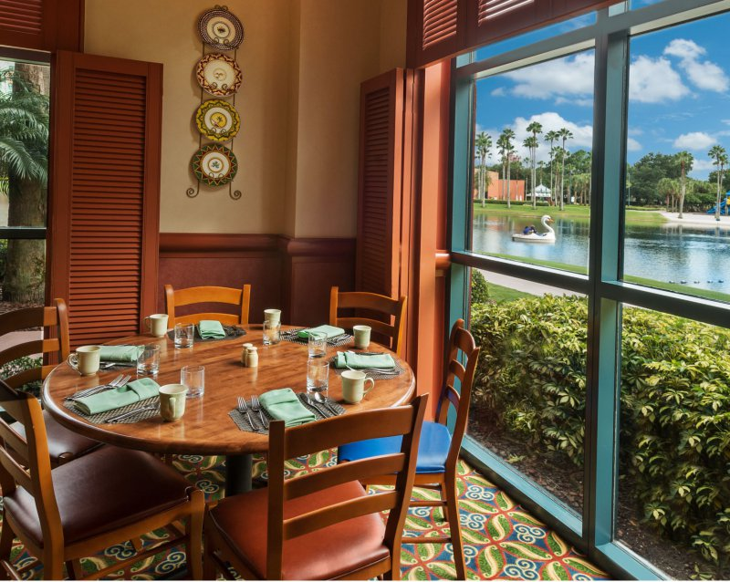 A dining table next to a window looking out at the lakeside while dining at Fresh at the Walt Disney World Dolphin Resort