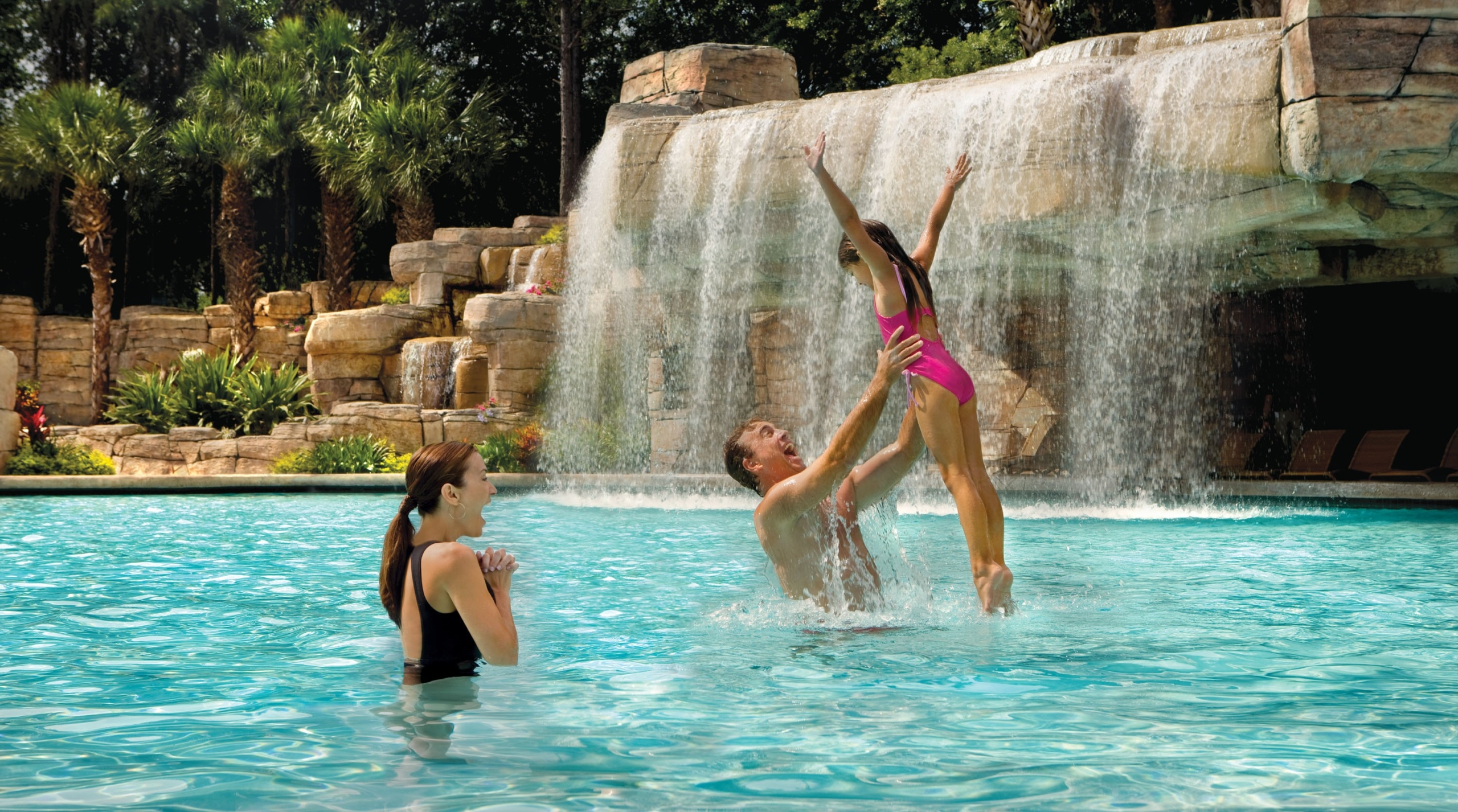 Dad throwing his daughter in the air in the grotto pool.